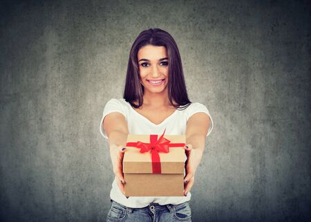 Portrait of a cute smiling girl giving a gift box looking at camera isolated on wall background