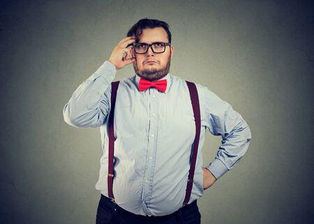 Porträt eines verwirrt denkenden molligen Geschäftsmannes, der nach oben schaut Standard-Bild