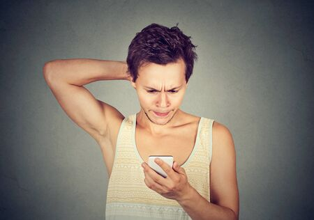 Portrait of a young man looking at mobile phone with confused expression on face Stock Photo