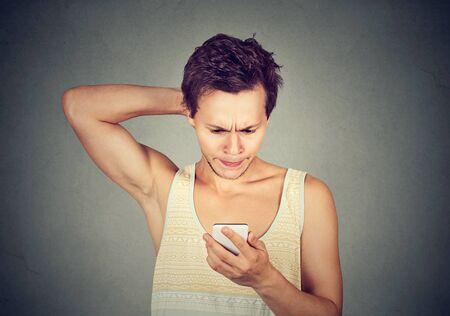 Retrato de un joven mirando el teléfono móvil con expresión confusa en la cara Foto de archivo