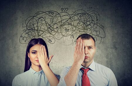 Half blindfolded couple a man and a woman having communication problems and share anxious thoughts  Stock Photo