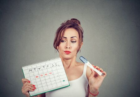 Doubtful young woman holding positive pregnancy test and her periods calendar  免版税图像