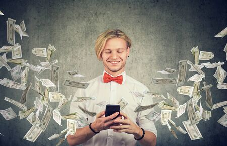 Happy young man using smartphone with dollar bills flying away from cellphone screen