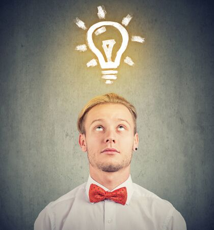 Young man with thoughtful expression and bright light bulb over his head Stock Photo