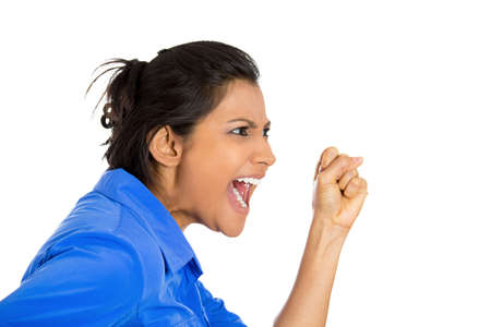 Closeup of an angry woman screaming with wide open mouth being hysterical