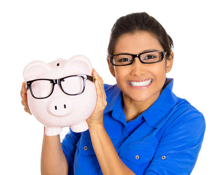Portrait of a young smiling woman wearing glasses holding giving a kiss to a piggy bank, isolated on white background.