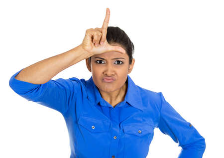 Portrait of a young woman displaying loser sign on her forehead and looking at camera with disgust