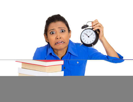 Portrait of a busy nervous young woman carrying stack of books and alarm clock feeling stressed from project deadline isolated on white background. Zdjęcie Seryjne