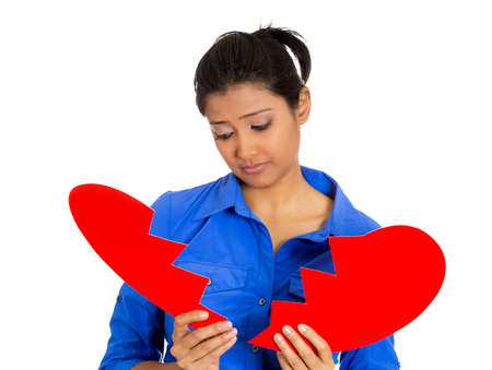 Portrait of a young sad, depressed, confused woman, holding broken heart in her hands isolated on white background.