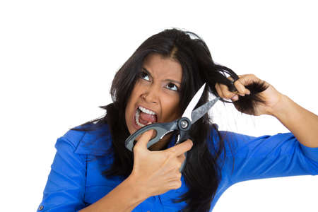 Closeup portrait of angry pissed off woman having bad day about to chop off her black hair with scissors, isolated on white background. Negative emotion facial expression feelings, attitudes