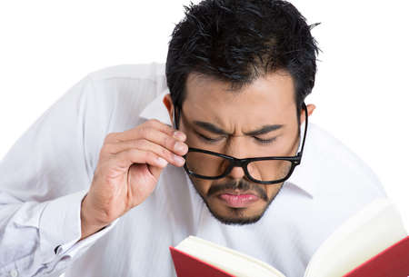 Closeup portrait of a young nerdy guy with big black eye glasses trying to read book but having difficulties seeing text because of vision problems.