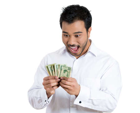 Closeup portrait, super happy excited successful young man holding money dollar bills in hand, isolated white background. Positive emotion facial expression feeling. Financial reward savings Zdjęcie Seryjne