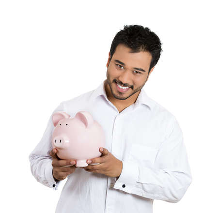 Closeup portrait of young smiling student, worker man holding piggy bank isolated on white background. Smart currency financial investment decisions. Budget management and savings