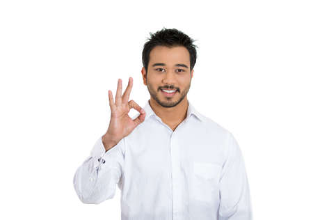 Closeup portrait of young handsome happy, smiling excited man giving OK sign with fingers, isolated on white background. Positive human emotions, facial expressions, feelings, symbols, body language