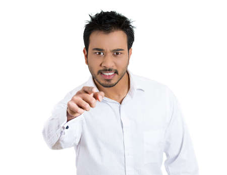 Closeup portrait of a young unhappy man, looking very angry, agitated, pointing with finger, isolated on white background. Negative human emotion facial expression feelings