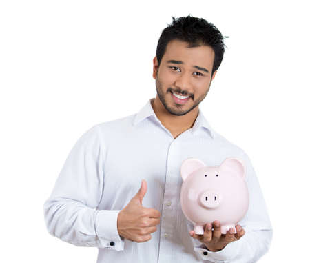Closeup portrait of young smiling student, worker man holding piggy bank, giving thumbs up, isolated on white background. Smart currency financial investment decisions. Budget management and savings
