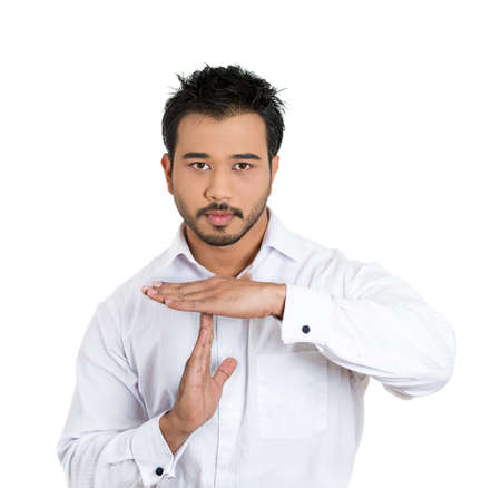 Closeup portrait of handsome young serious man showing a time out gesture with hands, isolated on white background. Negative human emotions, facial expressions, signs, symbols, body language, attitude