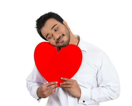 Closeup portrait of happy smiling handsome man holding large red heart to chest daydreaming of women in love ,isolated on white background. Positive emotion facial expression feelings