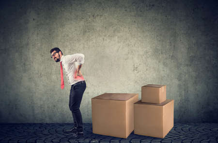 Young man suffering from back ache moving heavy boxes Zdjęcie Seryjne