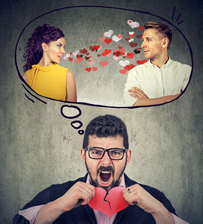 Stressed guy tearing in half red heart frustrated with his girlfriend flirting with another man