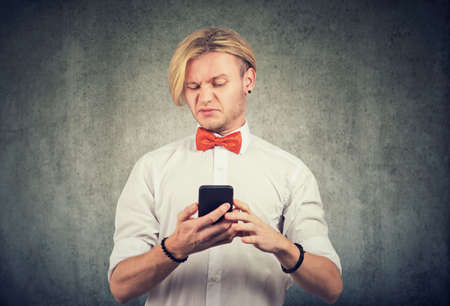 Portrait of a young annoyed man reading bad news on his smartphone