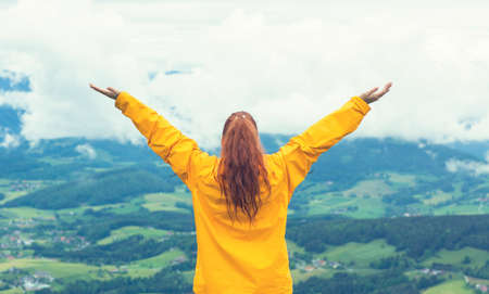 Happy young woman standing with arms raised at mountain peak