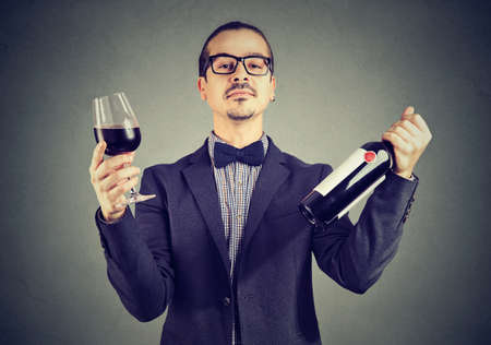 Portrait of a confident wine expert holding glass of red wine and a bottle Banque d'images