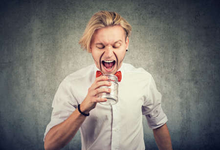 Portrait of an angry young man screaming into empty glass jar