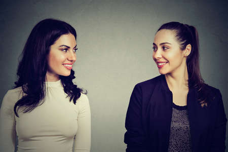 Portrait of two happy young women looking at each other