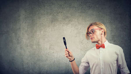Young man looking with magnifying glass isolated on wall background Banque d'images