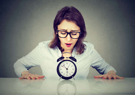Anxious young woman sitting at table looking at alarm clock Banque d'images
