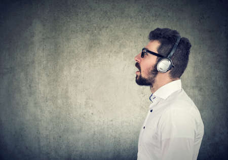 Side view of a young man with headphones listening to music Banque d'images