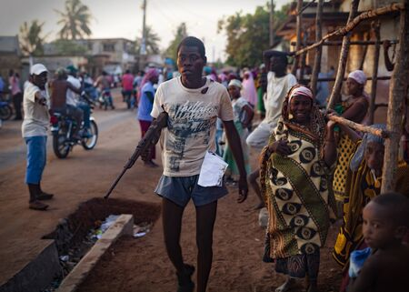 acts: Angoche, Mozambique - October 4, 2014: Armed man spotted during a Renamo rally for the 2014 presidential and parlamentary elections. Several incidents and acts of violence threatened the electoral process and disarmament of former soldiers is still a majo