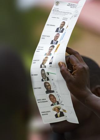 encuestando: Mbale, Uganda - 18 de febrero de 2011: el personal de sondeo que muestra papeletas marcadas con las fotos de los candidatos presidenciales en el proceso de recuento de votos durante elecciones generales de 2011 y presidenciales de Uganda