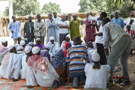 africa people: Gabu, Guinea-Bissau - May 9, 2014: village council meeting in rural africa with activists speaking to elders Editorial
