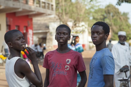 poor african: Gabu, Guinea-Bissau - March 28, 2014: Unidentified african boys gathering at the main street of a rural town