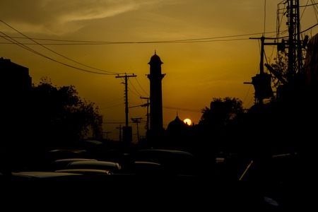 Mosque silhouette by sunset and in heavy traffic jam in Lahore, Pakistan