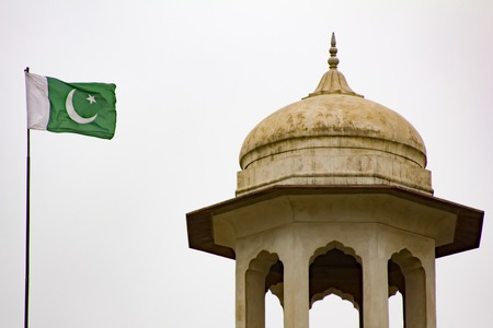 Pakistani flag and details of the Shahi Qila, the Lahore Fort built in the XVI century
