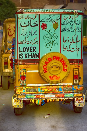 A three-wheeler taxi in Pakistan, also known as samosa, tempo, tuk-tuk, trishaw, autorick. Painted with flowers and urdu slogans
