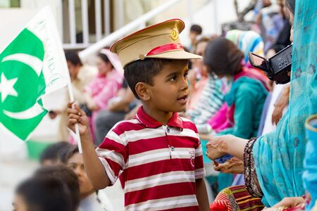 Lahore, Pakistan - May 5, 2013: Unidentified proud Pakistani kid with flag and military cap at a public celebration with his mother Redakční