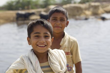 Lahore, Pakistan - May 9, 2013: Portrait of 2 pakistani boys playing by the river while shepherding cows in Lahore outskirts