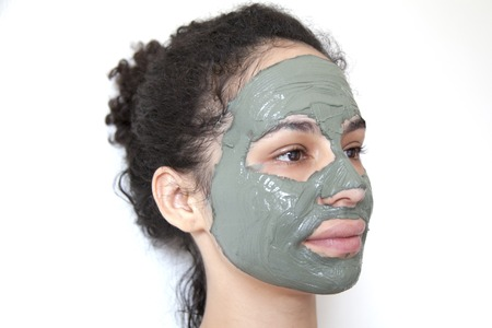 Beautiful young Brazilian model with green clay facial mask