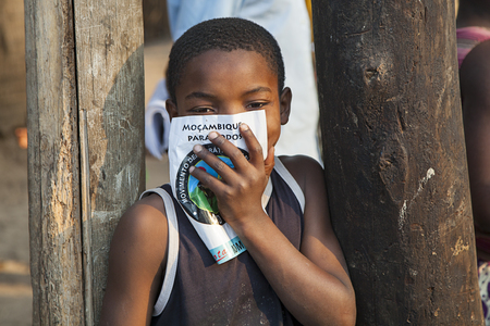 Nampula, Mozambique - October 10, 2014: Small kid from Northern Mozambique holding an electoral poster saying