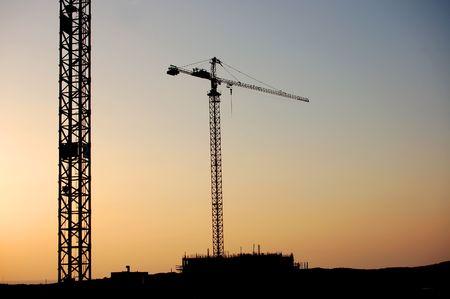 bouw plaats met twee kranen op de zons ondergang  Stockfoto