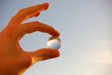 transcend: holding glass marble over blue sky