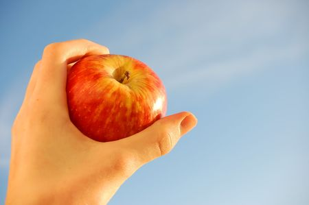 holding red apple over blue sky Stock Photo