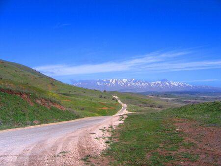weg die leidt naar besneeuwde bergen Stockfoto