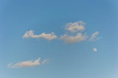 gibbous: Bright blue sky with clouds and waning gibbous moon