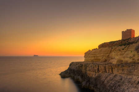 A beautiful sunset over the island of Filfla just outside Malta in the Mediterranean Sea  photo