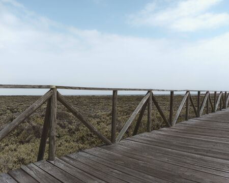 Perspective photo of the old bridge leading to the beach Zdjęcie Seryjne - 134164591